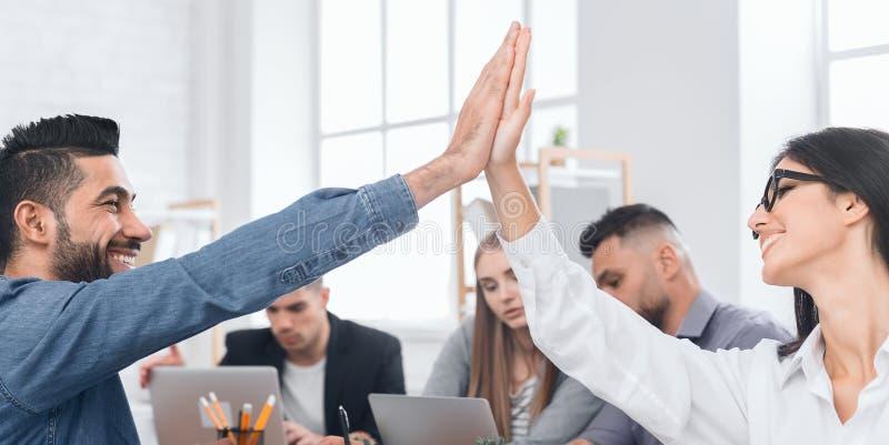 Bedrijfscollega's die hoge fives geven op vergadering stock fotografie