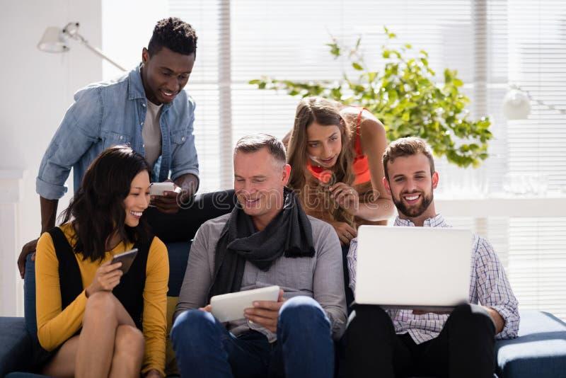 Bedrijfscollega's die met elkaar interactie aangaan terwijl het gebruiken van elektronische apparaten royalty-vrije stock foto
