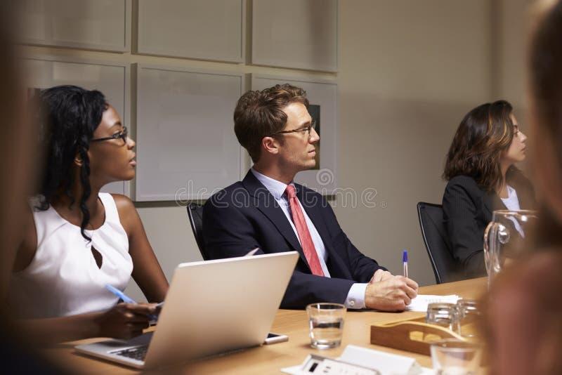 Bedrijfscollega's die op bestuurskamervergadering luisteren stock foto