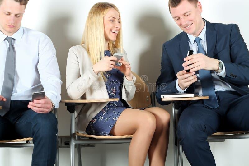 Bedrijfscollega's die op stoelen zitten en mobiele telefoon met behulp van Onderneemster het lachen royalty-vrije stock foto