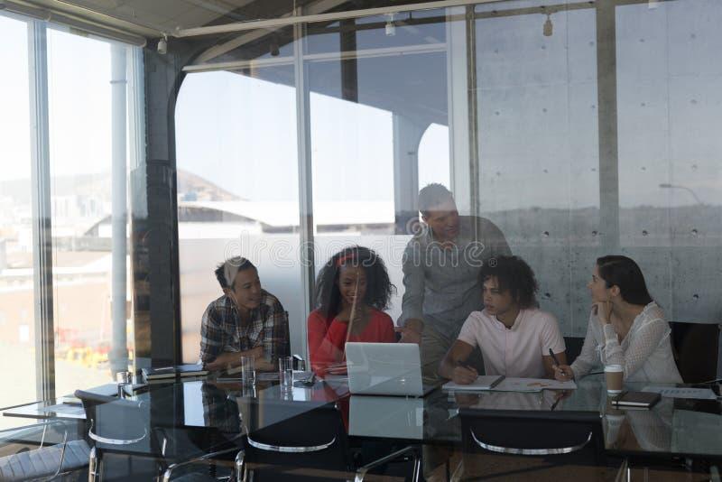 Bedrijfscollega's die over laptop in bureau bespreken royalty-vrije stock fotografie