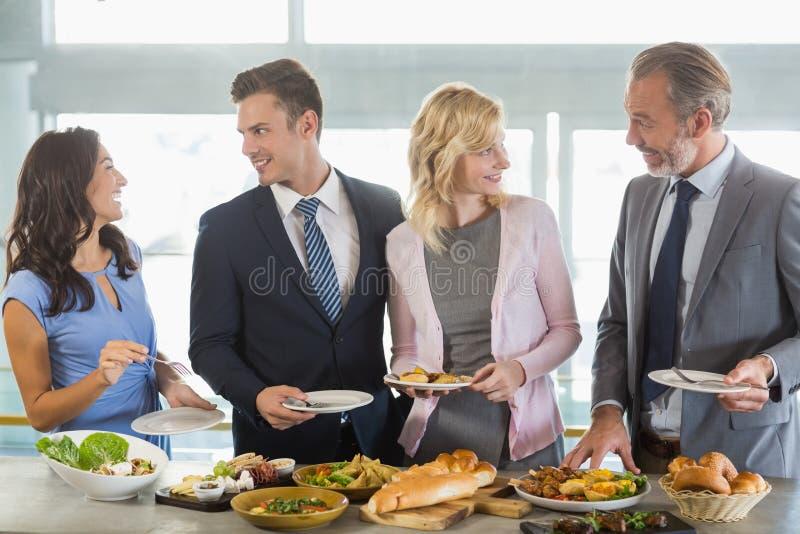 Bedrijfscollega's die terwijl het dienen van bij buffetlunch op elkaar inwerken royalty-vrije stock fotografie