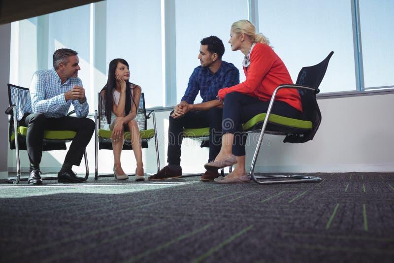Bedrijfscollega's die terwijl het zitten op stoelen op kantoor communiceren stock fotografie