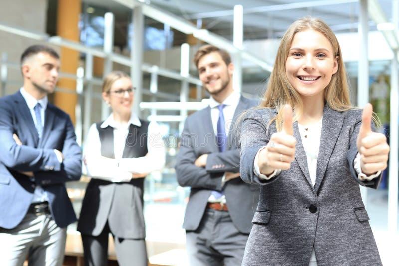 Bedrijfsconcept - de aantrekkelijke onderneemster met team in bureau het tonen beduimelt omhoog royalty-vrije stock foto's