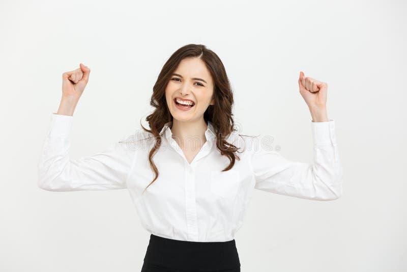 Bedrijfsconcept: de jonge gelukkige onderneemster met dient de lucht in viert succes op witte achtergrond stock fotografie