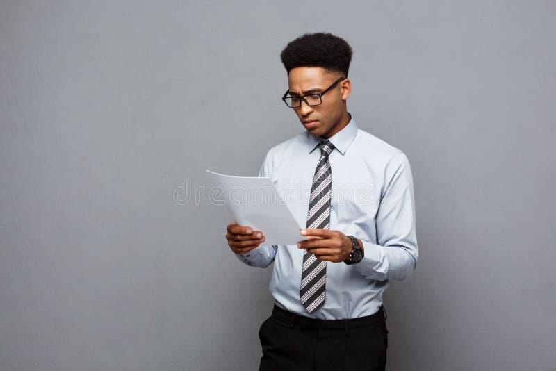 Bedrijfsconcept - de knappe jonge professionele Afrikaanse Amerikaanse zakenman concentreerde lezing op documentdocument stock fotografie