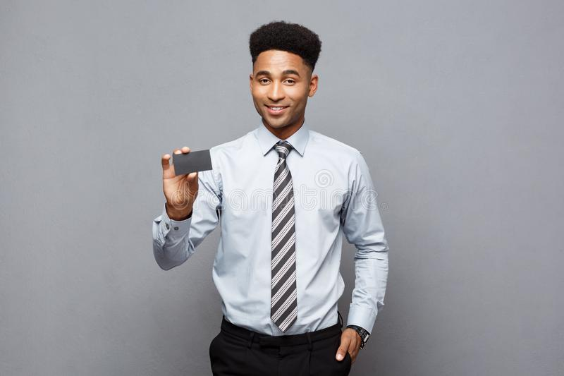Bedrijfsconcept - Gelukkige knappe professionele Afrikaanse Amerikaanse zakenman die naamkaart tonen aan cliënt stock foto's