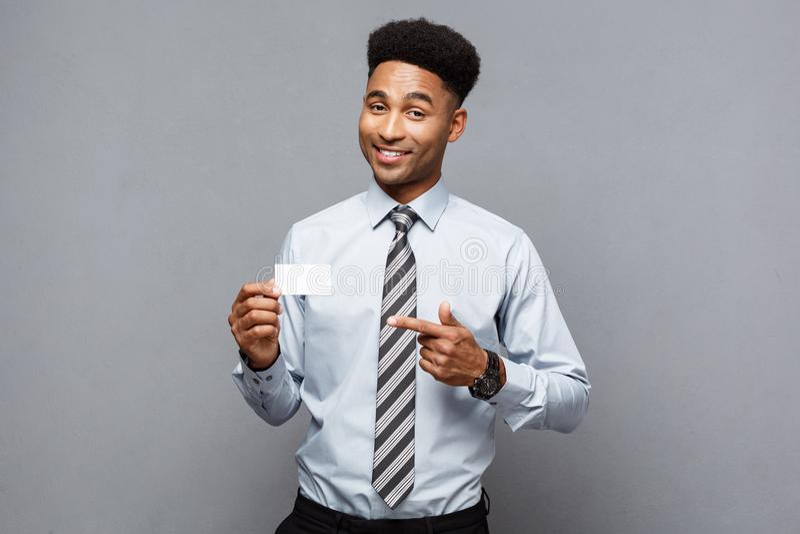 Bedrijfsconcept - Gelukkige knappe professionele Afrikaanse Amerikaanse zakenman die naamkaart tonen aan cliënt royalty-vrije stock afbeelding