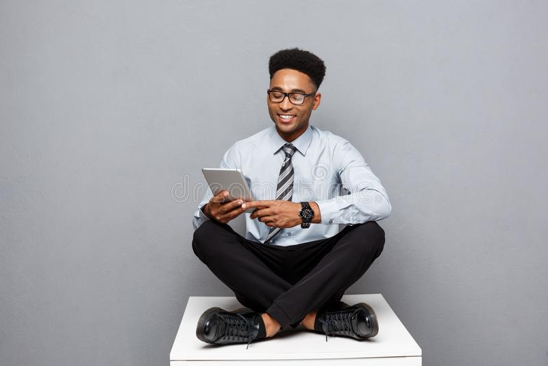 Bedrijfsconcept - het Gelukkige knappe professionele Afrikaanse Amerikaanse zakenman texting op digitale tablet aan cliënt stock fotografie