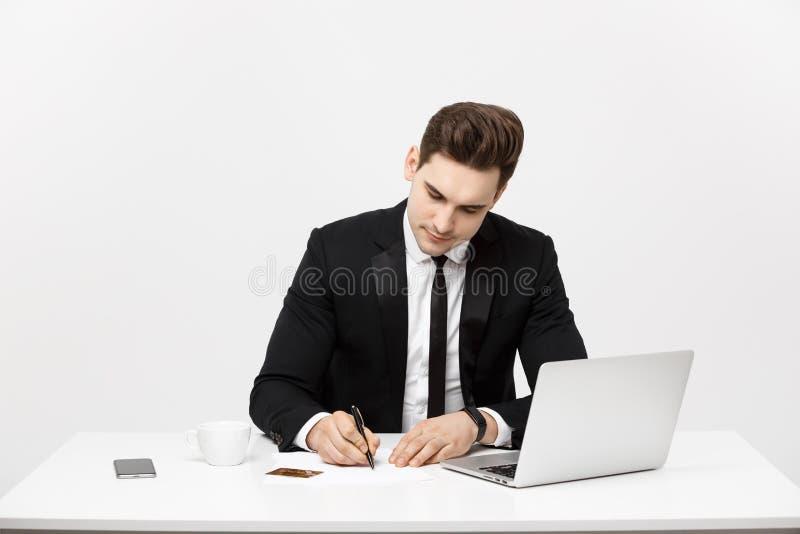 Bedrijfsconcept: Het portret concentreerde jonge succesvolle zakenman het schrijven documenten bij helder bureau royalty-vrije stock foto's