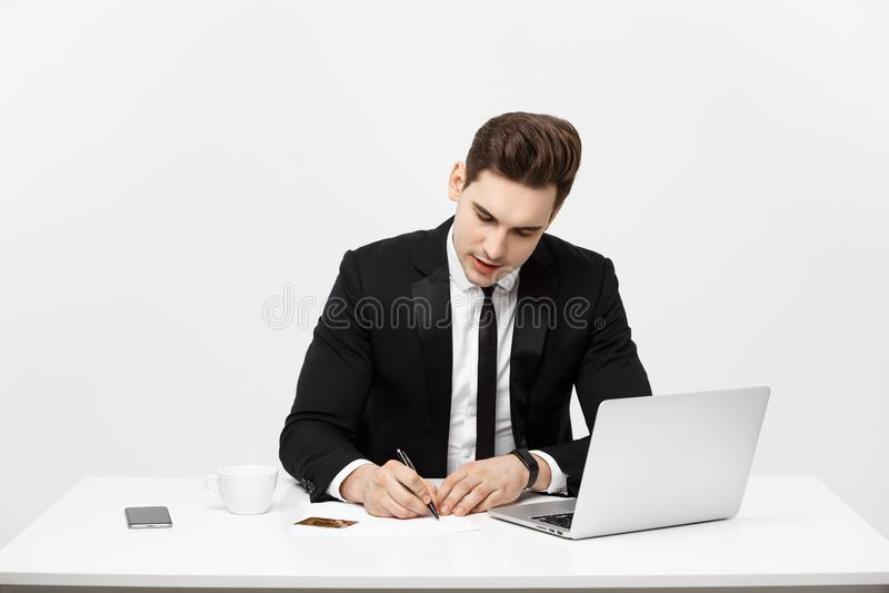Bedrijfsconcept: Het portret concentreerde jonge succesvolle zakenman het schrijven documenten bij helder bureau royalty-vrije stock afbeeldingen