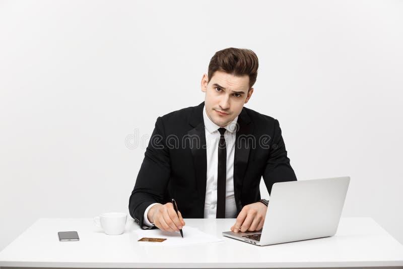 Bedrijfsconcept: Het portret concentreerde jonge succesvolle zakenman het schrijven documenten bij helder bureau stock fotografie