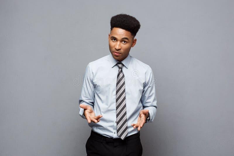 Bedrijfsconcept - het Zekere vrolijke jonge Afrikaanse Amerikaanse tonen dient voorzijde van hem met teleurgestelde uitdrukking i stock afbeelding