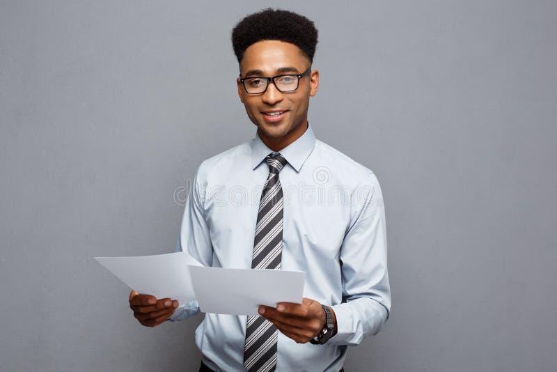 Bedrijfsconcept - knappe jonge professionele Afrikaanse Amerikaanse het rapportdocumenten van de zakenmanholding stock fotografie
