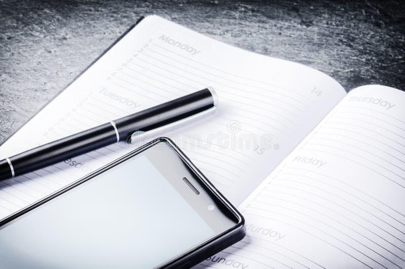 Bedrijfsconcept met agenda, mobiele telefoon en pen stock fotografie
