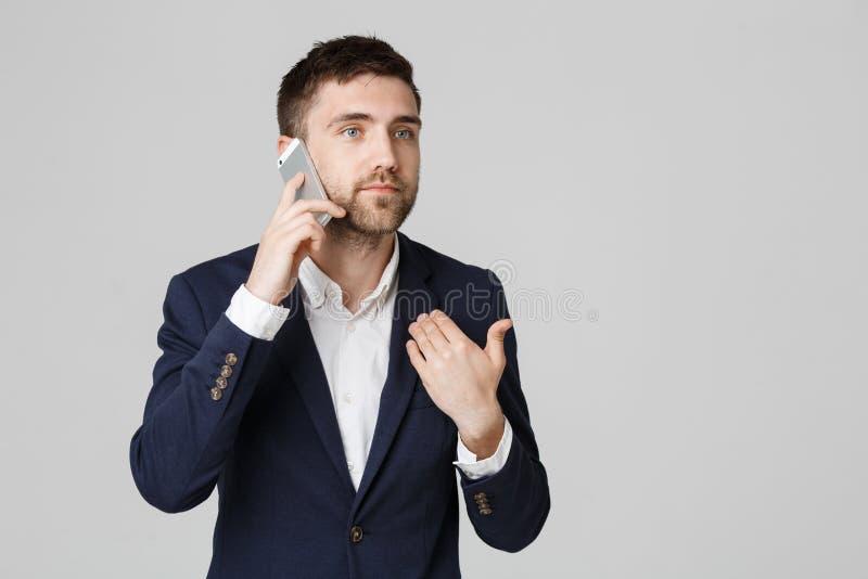 Bedrijfsconcept - Portret jonge knappe boze bedrijfsmens in kostuum die op telefoon spreken die camera bekijken wit royalty-vrije stock fotografie