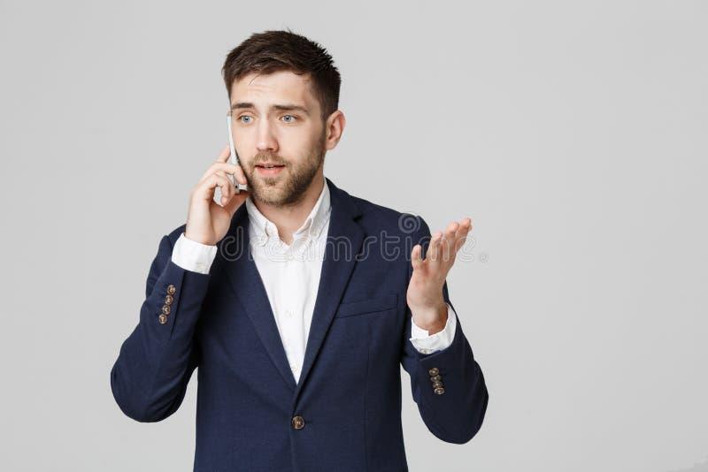 Bedrijfsconcept - Portret jonge knappe boze bedrijfsmens in kostuum die op telefoon spreken die camera bekijken wit stock foto's