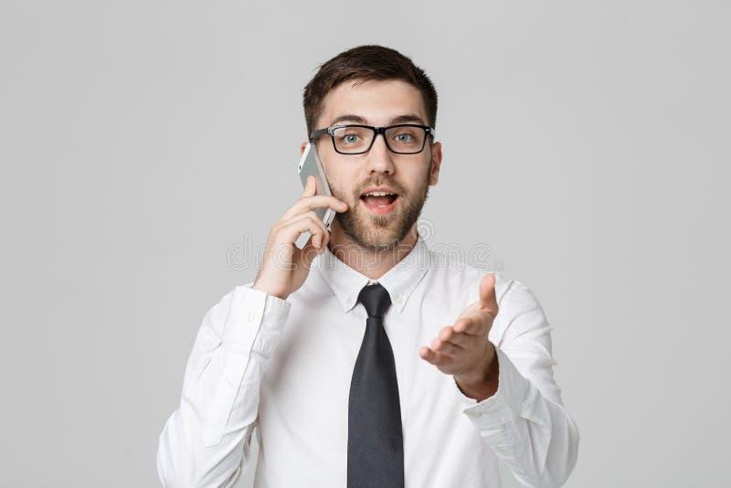 Bedrijfsconcept - Portret jonge knappe boze bedrijfsmens in kostuum die op telefoon spreken die camera bekijken Witte achtergrond royalty-vrije stock fotografie