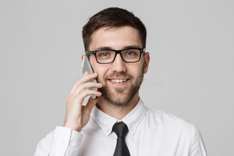 Bedrijfsconcept - Portret jonge knappe vrolijke bedrijfsmens in kostuum die op telefoon spreken die camera bekijken Witte achterg stock foto