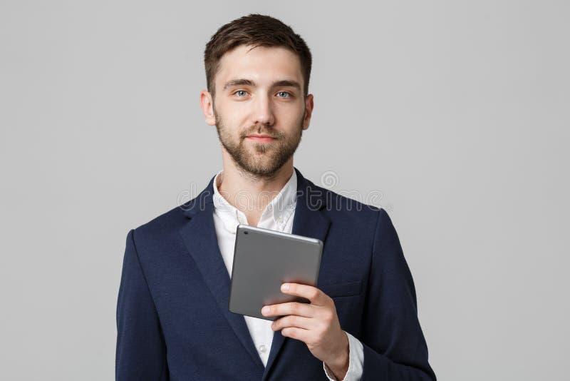 Bedrijfsconcept - Portret Knappe Bedrijfsmens die digitale tablet met het glimlachen zeker gezicht spelen Witte achtergrond De ru stock foto's