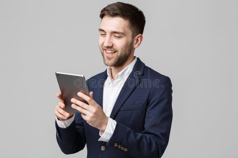 Bedrijfsconcept - Portret Knappe Bedrijfsmens die digitale tablet met het glimlachen zeker gezicht spelen Witte achtergrond De ru royalty-vrije stock afbeeldingen
