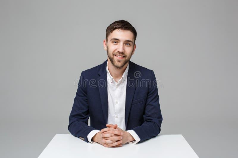 Bedrijfsconcept - Portret knappe gelukkige knappe bedrijfsmens in kostuum die en in het werkbureau glimlachen situeren Witte acht royalty-vrije stock foto