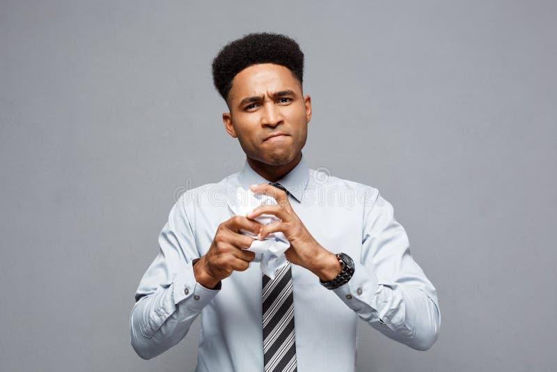Bedrijfsconcept - portret van ernstige Afrikaanse Amerikaanse zakenmanholding die rapportdocumenten op handen verfrommelen stock foto