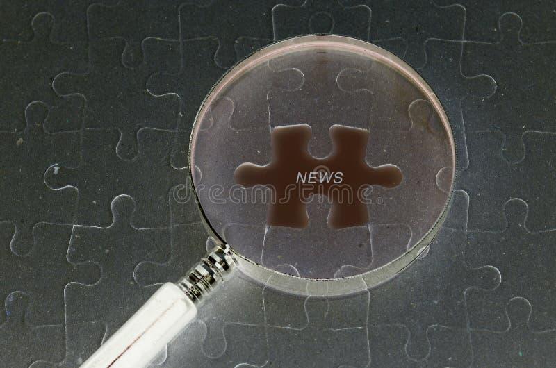 Bedrijfsconcept: Puzzelachtergrond en vergrootglas en copyspace gebied met NIEUWSwoord stock foto