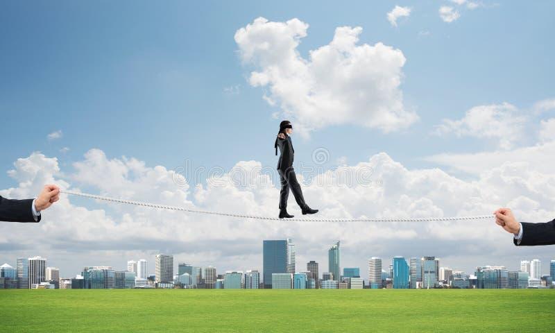 Bedrijfsconcept risicosteun en hulp met mens het in evenwicht brengen op kabel royalty-vrije stock fotografie