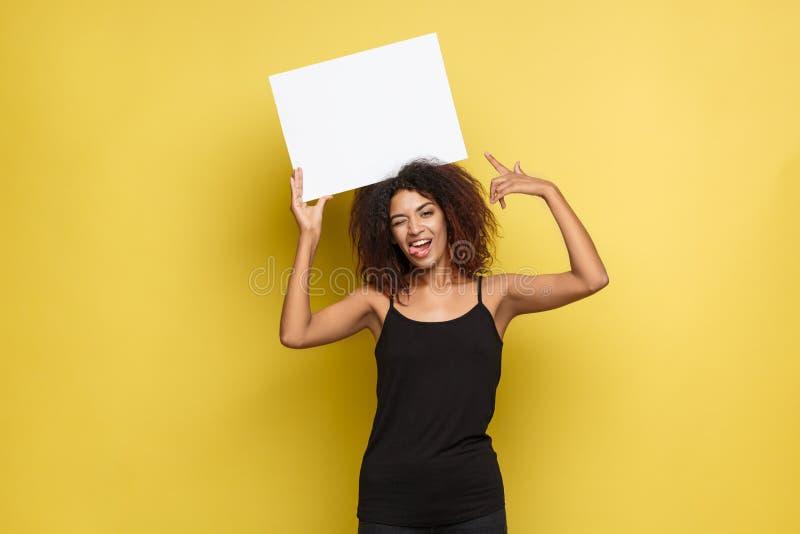 Bedrijfsconcept - sluit omhoog Portret jonge mooie aantrekkelijke Afrikaanse Amerikaan glimlachend tonend duidelijk wit leeg teke stock afbeeldingen