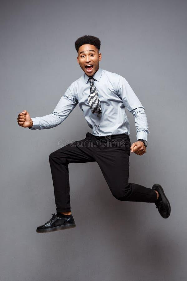 Bedrijfsconcept - Volledig lengteportret van het succesvolle Afrikaanse Amerikaanse zakenman gelukkige springen in het bureau stock fotografie
