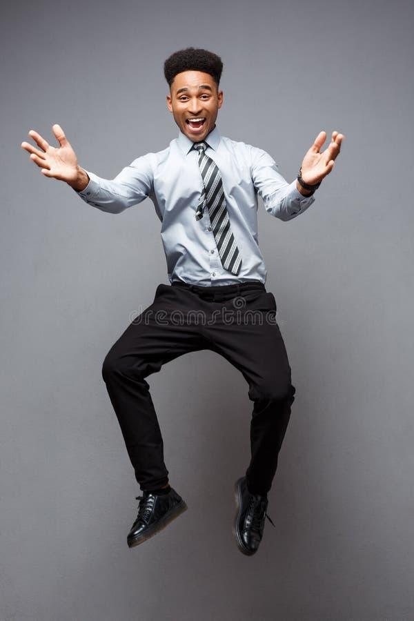 Bedrijfsconcept - Volledig lengteportret van het succesvolle Afrikaanse Amerikaanse zakenman gelukkige springen in het bureau stock afbeeldingen