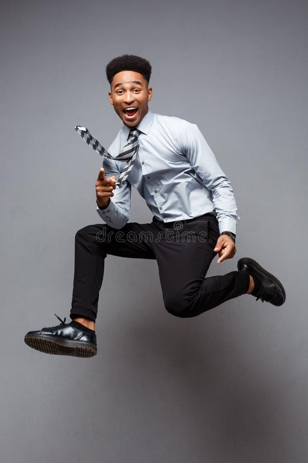 Bedrijfsconcept - Volledig lengteportret van het succesvolle Afrikaanse Amerikaanse zakenman gelukkige springen in het bureau royalty-vrije stock afbeeldingen