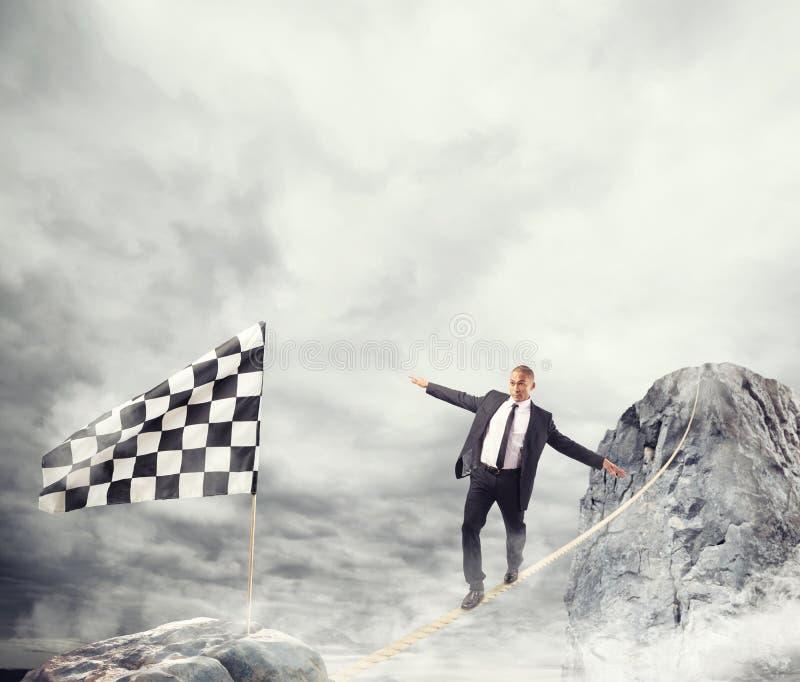 Bedrijfsconcept zakenman die de moeilijkheden overwinnen die de vlag op een kabel bereiken stock fotografie