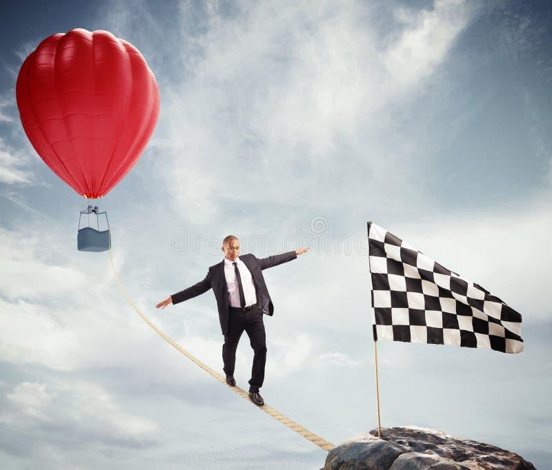 Bedrijfsconcept zakenman die de moeilijkheden overwinnen die de vlag op een kabel bereiken stock afbeelding