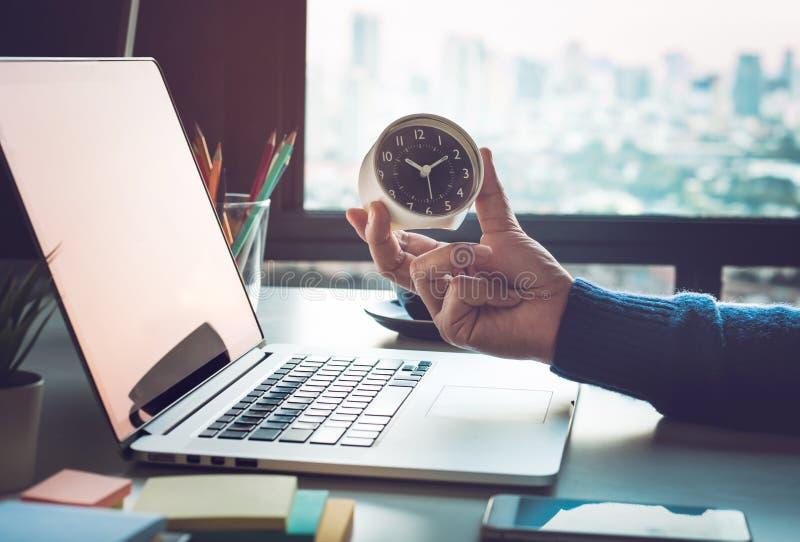 Bedrijfsconcepten met de klok van de zakenmanholding op computerlaptop Voor investeringsanalyse, die aan succes wachten stock afbeelding