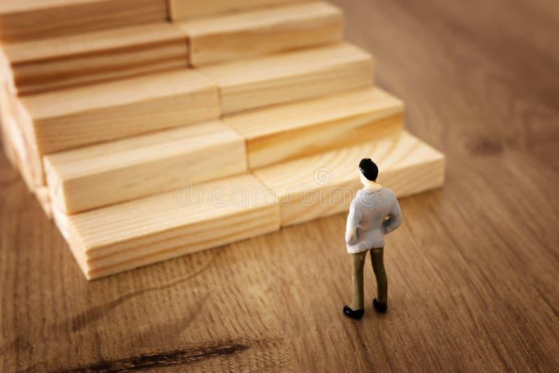 Bedrijfsconceptenbeeld van onderwijs en uitdaging Een mens bekijkt houten stappen en moet over zijn toekomst beslissen stock foto
