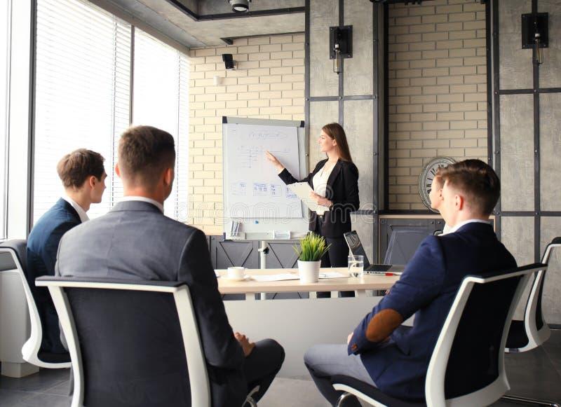 Bedrijfsconferentiepresentatie met team opleidings flipchart bureau stock fotografie