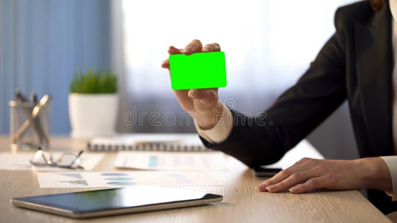 Bedrijfsdame die adreskaartje met groen gebied, de advertentie van de bankwezendiensten tonen royalty-vrije stock foto's