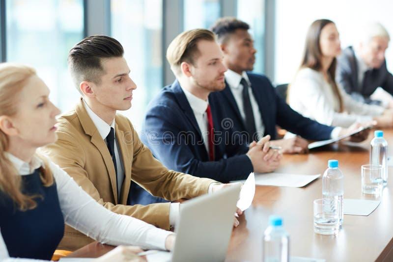 Bedrijfsdiemensen op informatie worden geconcentreerd stock foto's