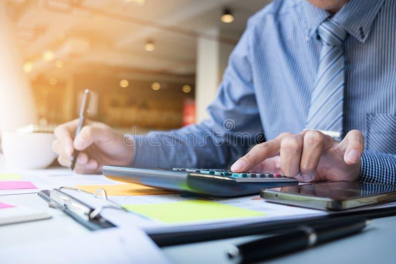 Bedrijfsfinanciënmens het berekenen begrotingsaantallen, Rekeningen en FI stock afbeelding