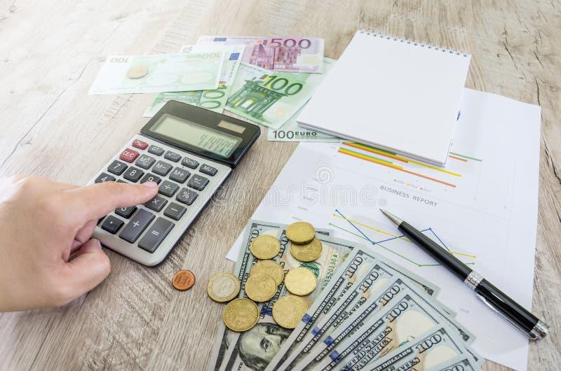 Bedrijfsgrafieken, euro, dollars, calculators en muntstukken De hand typt iets op de calculator royalty-vrije stock fotografie
