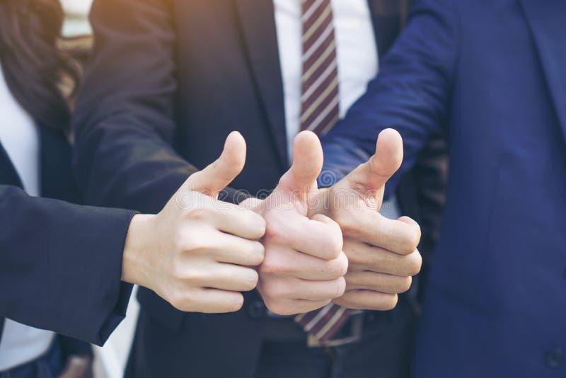 Bedrijfsgroepswerkpartners die omhoog Succesvolle Duim geven stock fotografie