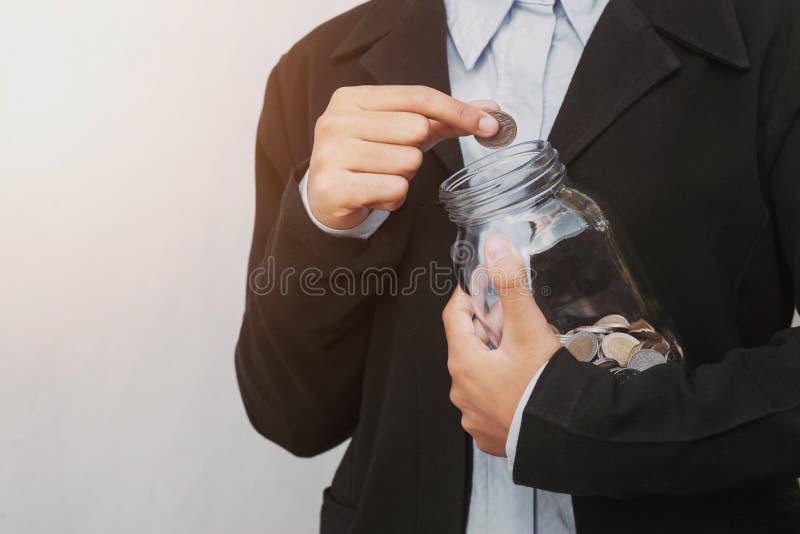 bedrijfshand die muntstukken in glaskruik zetten voor besparingsgeld accoun royalty-vrije stock afbeeldingen
