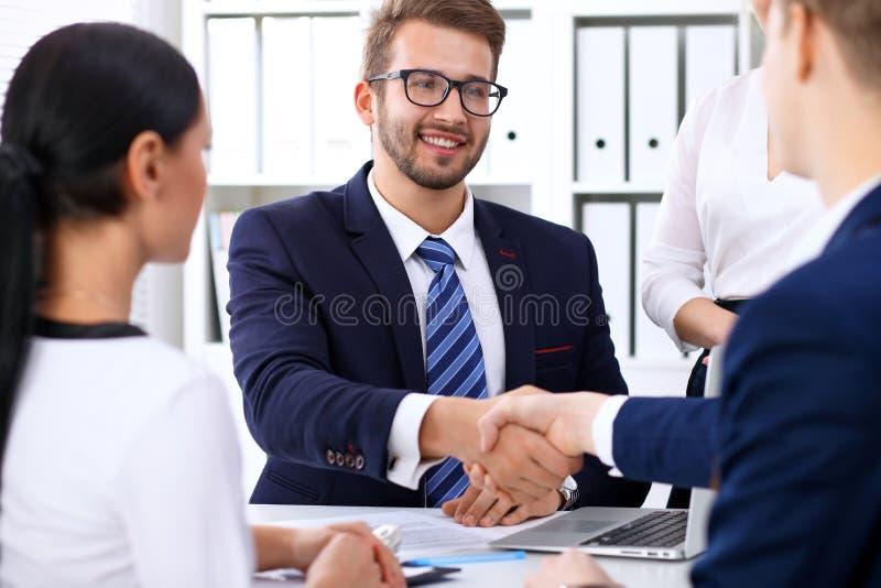 Bedrijfshanddruk bij vergadering of onderhandeling in het bureau De partners zijn tevreden omdat het ondertekenen of financieel a stock foto's