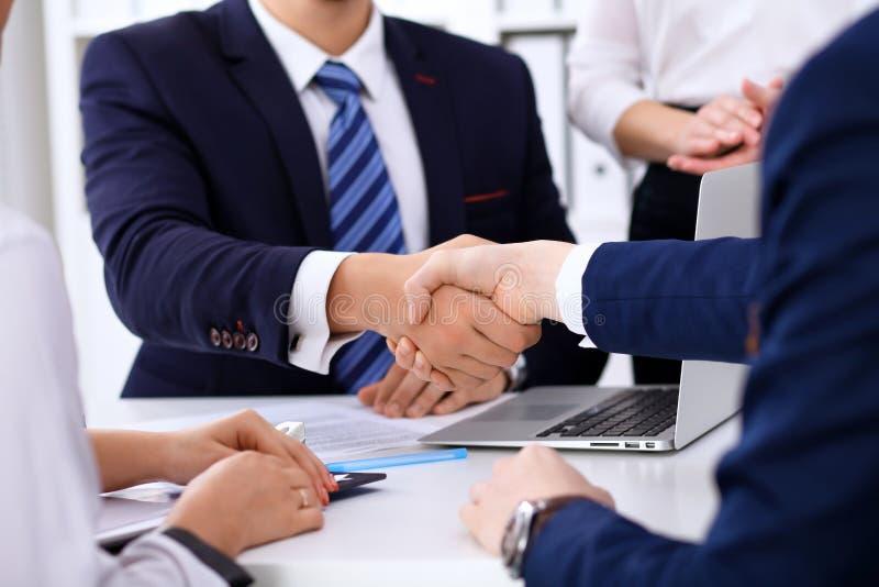 Bedrijfshanddruk bij vergadering of onderhandeling in het bureau De partners zijn tevreden omdat het ondertekenen of financieel a royalty-vrije stock afbeeldingen