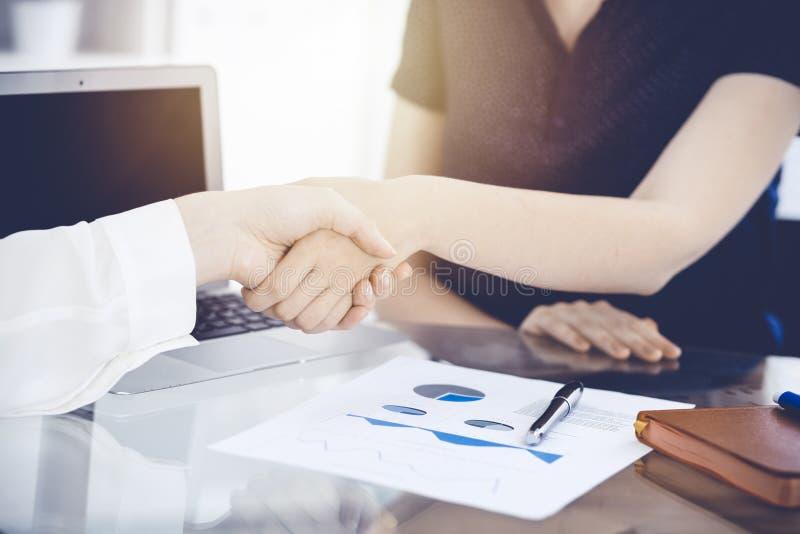 Bedrijfshanddruk na contract het ondertekenen Twee vrouwen die handen na het samenkomen of onderhandeling schudden Toevallige sti royalty-vrije stock foto