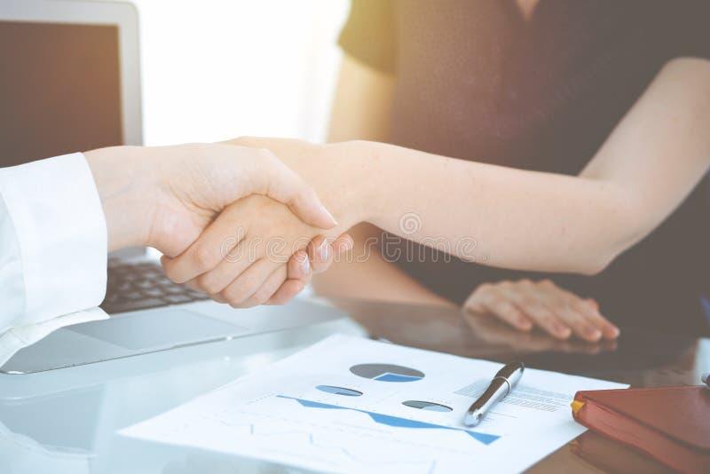 Bedrijfshanddruk na contract het ondertekenen Twee vrouwen die handen na het samenkomen of onderhandeling schudden Toevallige sti stock afbeelding