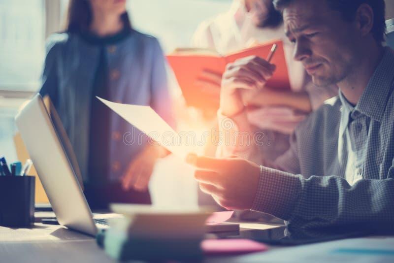 Bedrijfsideevergadering Op de markt brengend team die nieuw werkplan bespreken Laptop en administratie in open plekbureau royalty-vrije stock afbeelding