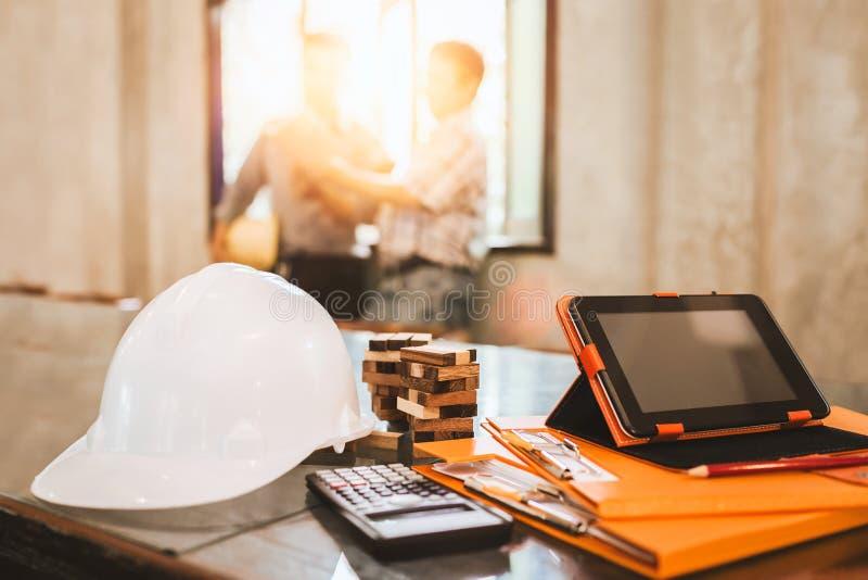 Bedrijfsingenieur die hard bij zijn bureau in bui van het flathuis werken stock foto